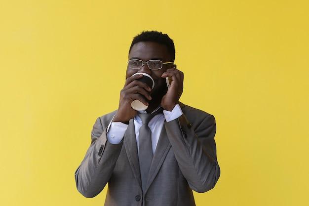 Afroamerikaner trinkt kaffee und spricht am telefon, auf gelbem hintergrund
