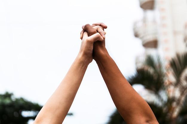 Afroamerikaner und weiße, die händchen halten, die nach oben ausgestreckt sind