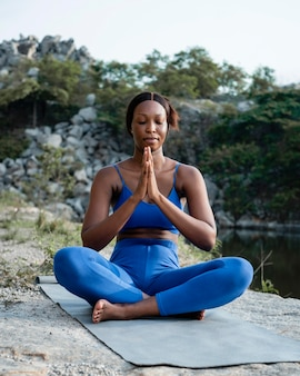 Afroamerikaner-yogalehrer, der im freien übt