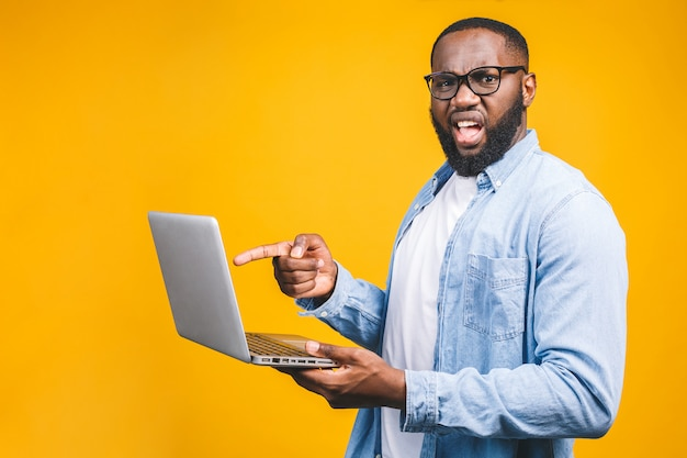 Afroamerikaner ypung mann erschreckte eine schlechte nachricht auf seinem laptop, isoliert gegen gelben hintergrund.