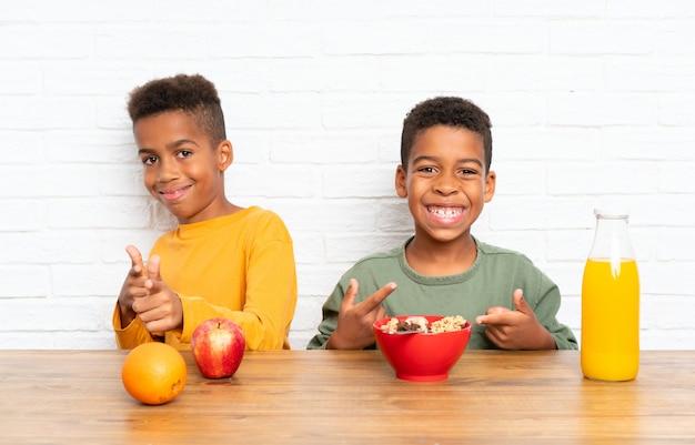Afroamerikanerbrüder, die frühstücken und auf die front zeigen