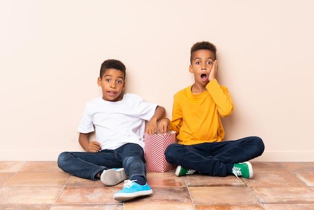 Afroamerikanerbrüder, die popcorn halten und überraschungsgeste tun