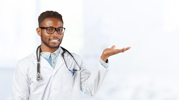 Afroamerikanerdoktor mit einem stethoskop, das gegen unscharf steht