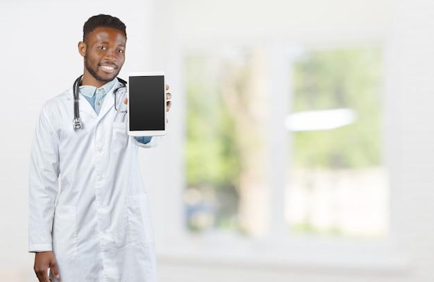 Afroamerikanerdoktor mit einem stethoskop, das gegen unscharfen hintergrund steht