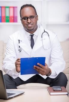 Afroamerikanerdoktor sitzt in seinem büro