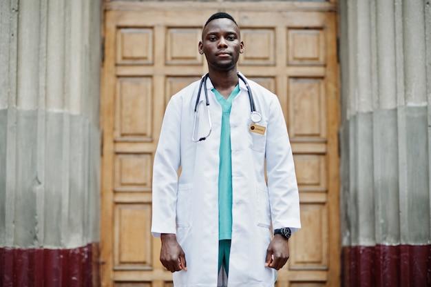 Afroamerikanerdoktormann am laborkittel mit dem stethoskop im freien gegen kliniktür.