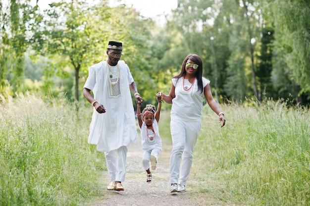 Afroamerikanerfamilie am weißen nigerianischen nationalkostüm, das den spaß im freien hat