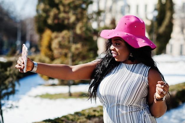 Afroamerikanerfrau am hut gehend auf straßen mit telefon auf händen.