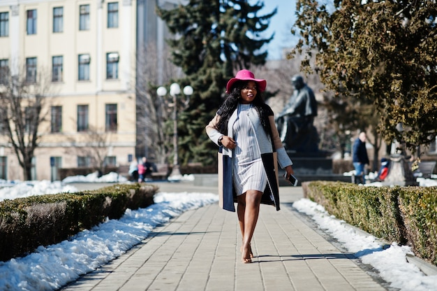 Afroamerikanerfrau am hut und am mantel mit telefon gehend an den straßen.