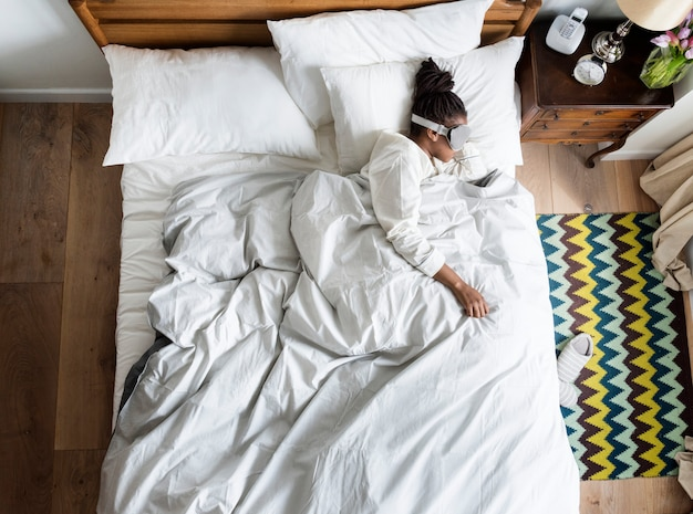 Afroamerikanerfrau auf bett schlafend mit einer augenabdeckung