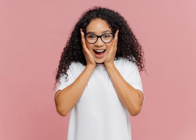 Afroamerikanerfrau berührt wangen, reagiert auf gute nachrichten, trägt transparente brille und weißes hemd