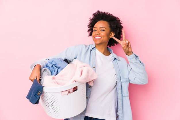 Afroamerikanerfrau des mittelalters, die wäsche isoliert macht, zeigt siegeszeichen und lächelt breit.
