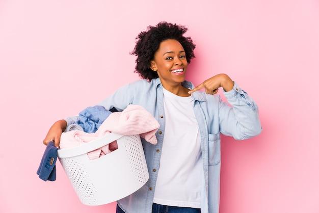 Afroamerikanerfrau des mittelalters, die wäsche tut, die isoliert überrascht auf sich selbst zeigt und breit lächelt.