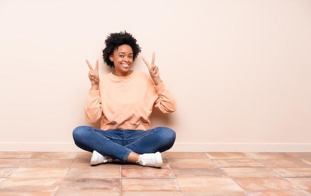 Afroamerikanerfrau, die auf dem boden sitzt