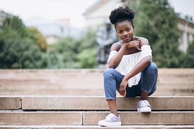Afroamerikanerfrau, die auf treppe durch die universität sitzt