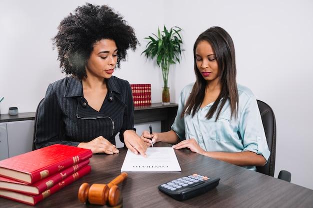 Afroamerikanerfrau, die bei tisch auf dokument nahe dame mit stift zeigt