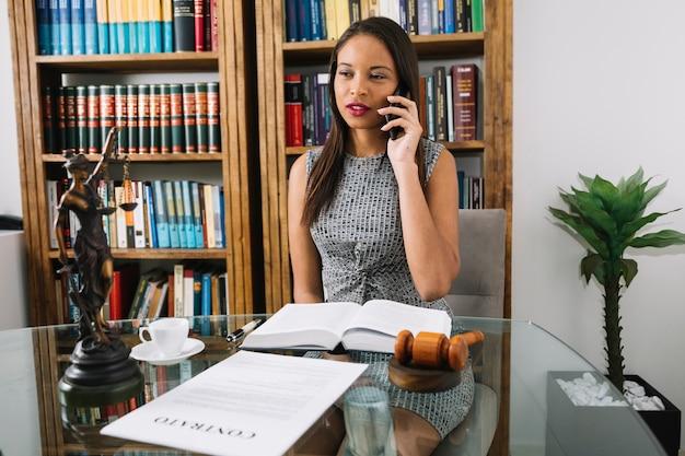 Afroamerikanerfrau, die bei tisch auf smartphone im büro spricht