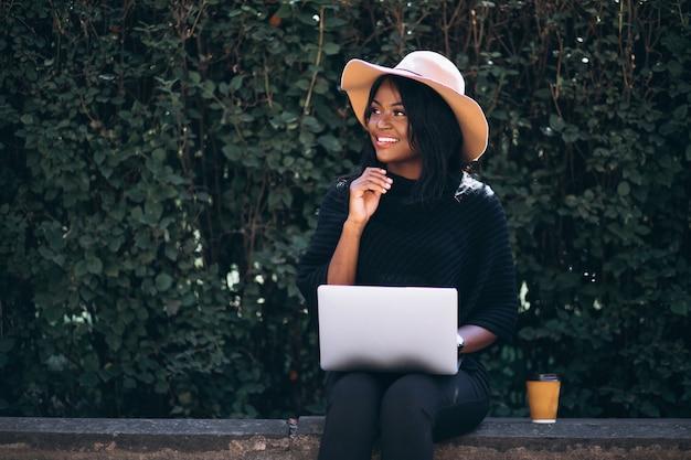 Afroamerikanerfrau, die draußen an einem computer arbeitet