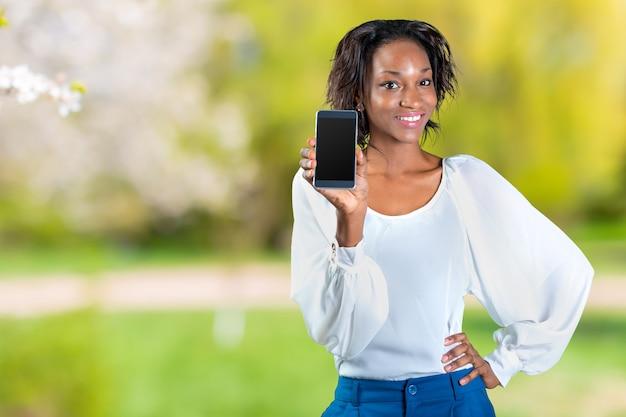 Afroamerikanerfrau, die ein mobiltelefon zeigt