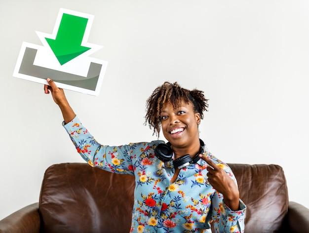 Afroamerikanerfrau, die eine downloadzeichenmusik und ein downloadkonzept hält