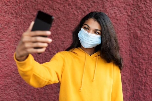 Afroamerikanerfrau, die eine medizinische maske trägt und ein selfie nimmt