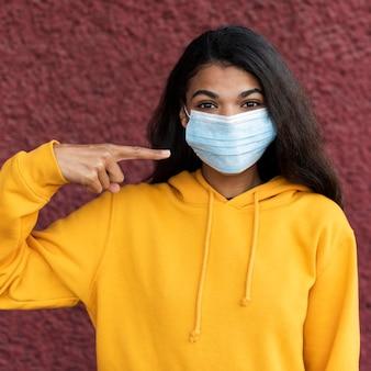 Afroamerikanerfrau, die eine medizinische maske trägt