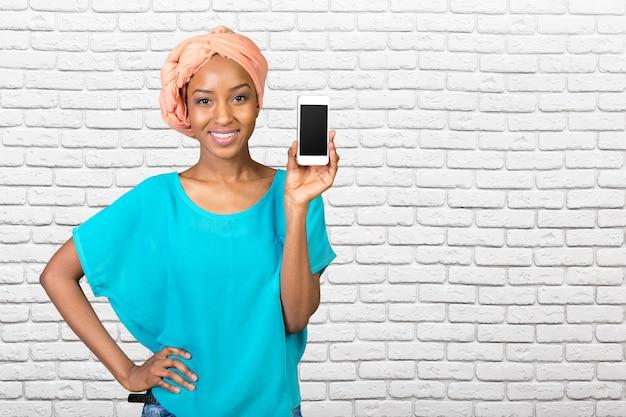 Afroamerikanerfrau, die einen handy zeigt