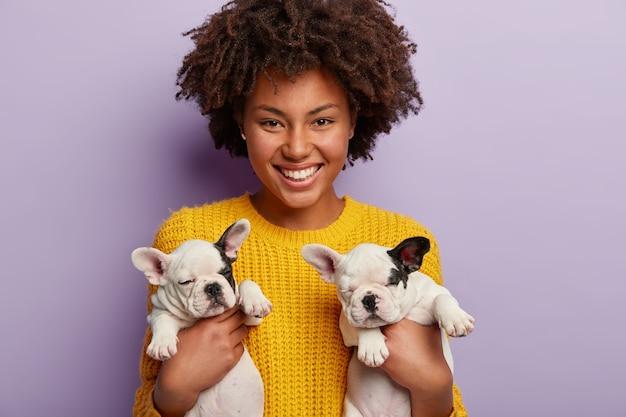 Afroamerikanerfrau, die gelben pullover hält, der welpen hält