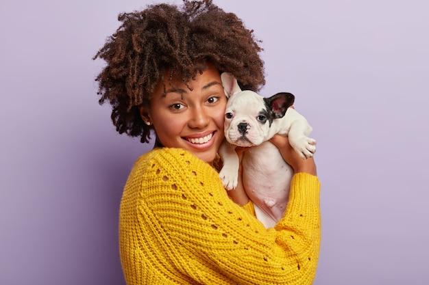 Afroamerikanerfrau, die gelben pullover hält welpen hält