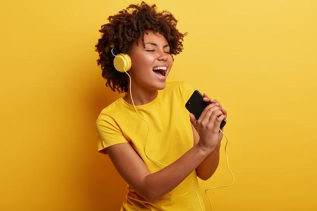 Afroamerikanerfrau, die gelbes t-shirt und kopfhörer trägt
