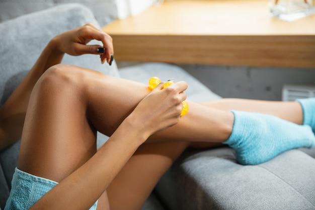 Afroamerikanerfrau, die handtuch trägt, das ihre tägliche hautpflege-routine zu hause tut.