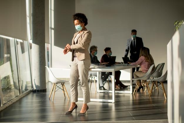 Afroamerikanerfrau, die im amt steht und maske als schutz vor koronavirus trägt