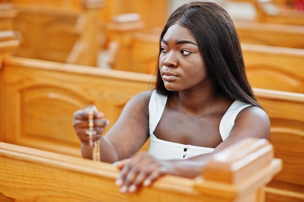 Afroamerikanerfrau, die in der kirche betet. der gläubige meditiert in der kathedrale und in der spirituellen zeit des gebets. afro mädchen halten rosenkranz und sitzen auf der bank.