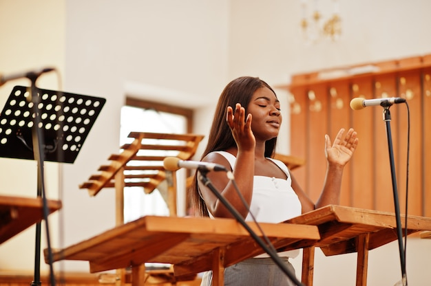 Afroamerikanerfrau, die in der kirche betet. die gläubigen meditieren in der kathedrale und in der spirituellen zeit des gebets. afro-mädchen, das gott auf chören singt und verherrlicht.