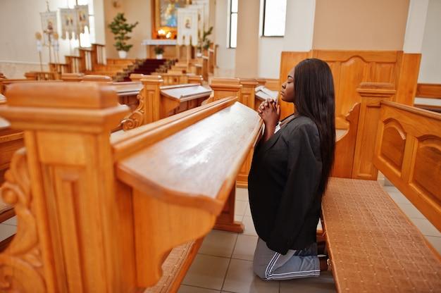 Afroamerikanerfrau, die in der kirche betet. die gläubigen meditieren in der kathedrale und in der spirituellen zeit des gebets. afro mädchen kniet.
