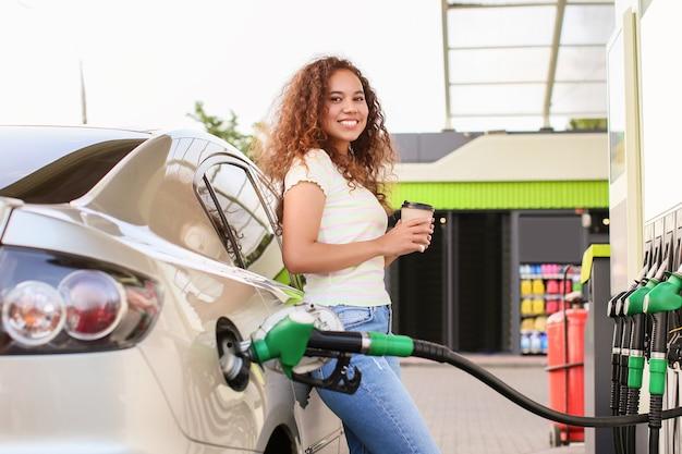 Afroamerikanerfrau, die kaffee trinkt, während autotank an der tankstelle auffüllt