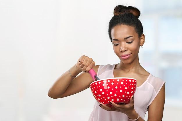 Afroamerikanerfrau, die küchengeräte hält
