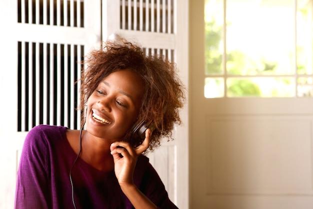 Afroamerikanerfrau, die musik auf kopfhörern hört