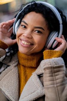 Afroamerikanerfrau, die musik in kopfhörern hört