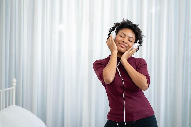 Afroamerikanerfrau, die musik mit ihren kopfhörern im wohnzimmer hört