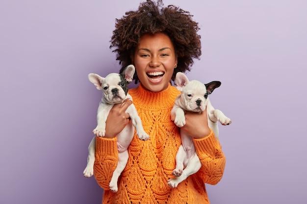 Afroamerikanerfrau, die orange pullover hält welpen hält