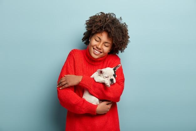 Afroamerikanerfrau, die roten pullover hält hund hält