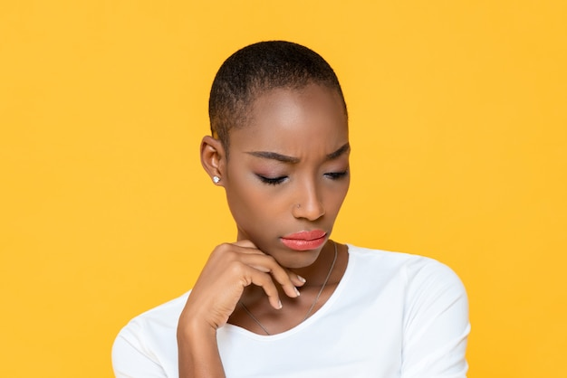 Afroamerikanerfrau, die sich traurig und gelangweilt fühlt, die unten mit der hand auf kinn lokalisiert auf gelber wand schaut