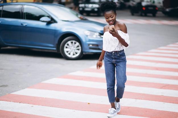 Afroamerikanerfrau, die straße mit telefon kreuzt