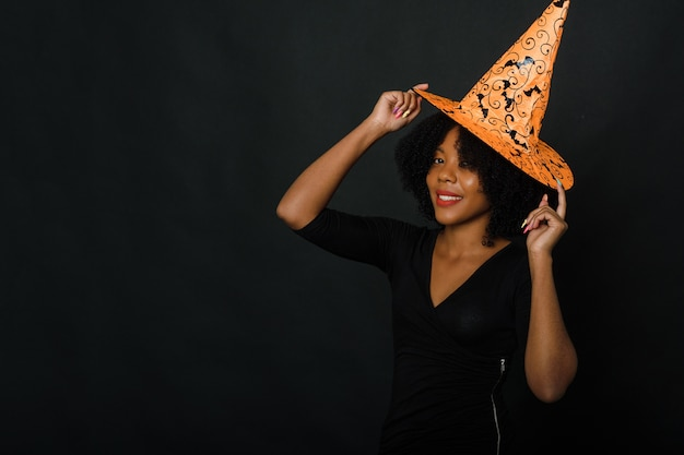 Afroamerikanerfrau im halloween-outfit auf schwarzem hintergrund