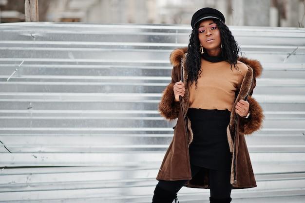 Afroamerikanerfrau im schaffellmantel und in der kappe warf am wintertag auf