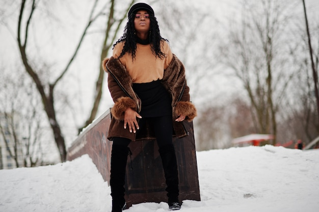Afroamerikanerfrau im schaffellmantel und in der kappe warf am wintertag gegen schneebedeckten hintergrund auf.
