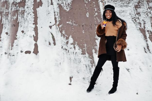 Afroamerikanerfrau im schaffellmantel und in der kappe warf am wintertag gegen schneebedeckten hintergrund mit tasse kaffee auf.