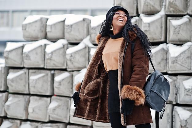 Afroamerikanerfrau im schaffellmantel und in der kappe warf am wintertag gegen schneebedeckten steinhintergrund auf.
