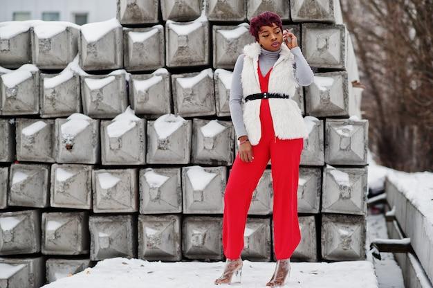 Afroamerikanerfrau in den roten hosen und in der weißen pelzmanteljacke warf am wintertag gegen schneebedeckten steinhintergrund auf.